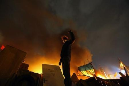 An anti-government protester rises his fist behind burning barricades in Kiev's Independence Square