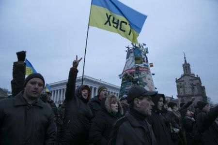 Ukrainians react to a speech in Kiev's Independence Square