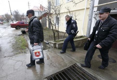 An election official carries a mobile ballot box at a house during voting in a referendum at the village of Pionerskoye in Simferopol