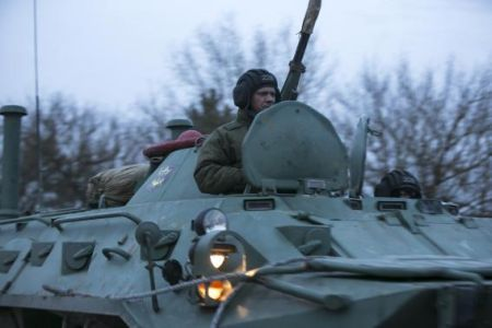 A Russian soldier sits on top of a military armoured personnel carrier (APC) as they drive on the road from Sevastopol to Simferopol