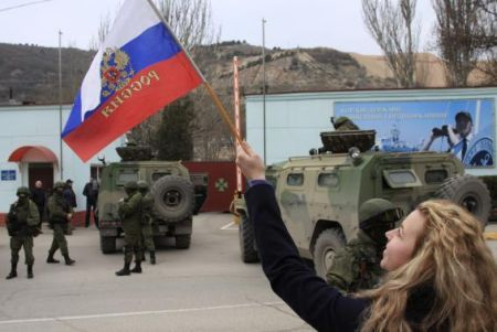 A woman waves a Russian flag as armed servicemen wait near Russian military vehicles outside a Ukrainian border guard post in the Crimean town of Balaclava