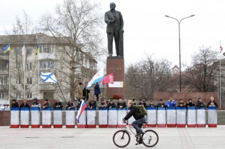 A man rides a bicycle in front of a statue of Soviet state founder Vladimir Lenin, guarded by people with shields in the Crimean city of Simferopol