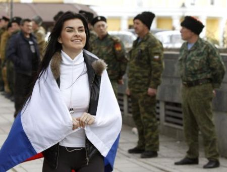 Pro-Russian supporter with the Russian national flag on her shoulders takes part in a meeting in Simferopol