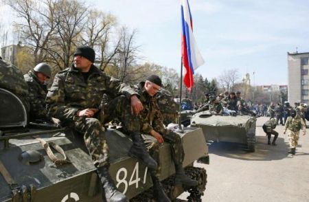 Armed men sit on an armoured personnel carrier with a Russian flag on it in Slaviansk
