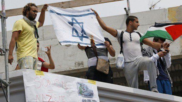 """19 iulie, Paris - Protestarii ard un steag israelian pe un acoperiș unde se află o pancartă pe care scrie """"sionism = nazism""""."""