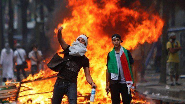 19 iulie, Paris - Un protestatar aruncă o piatră către polițiști