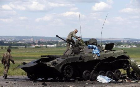 Ukrainian soldiers check a destroyed armoured vehicle at Slaviansk